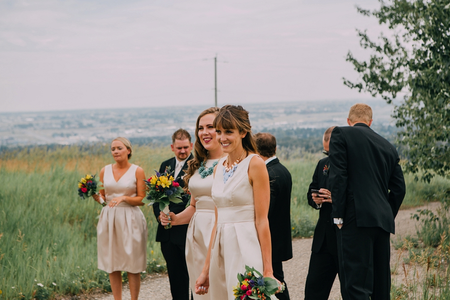 bridesmaids looking at bride and groom nose hill park calgary wedding photographer anna michalska