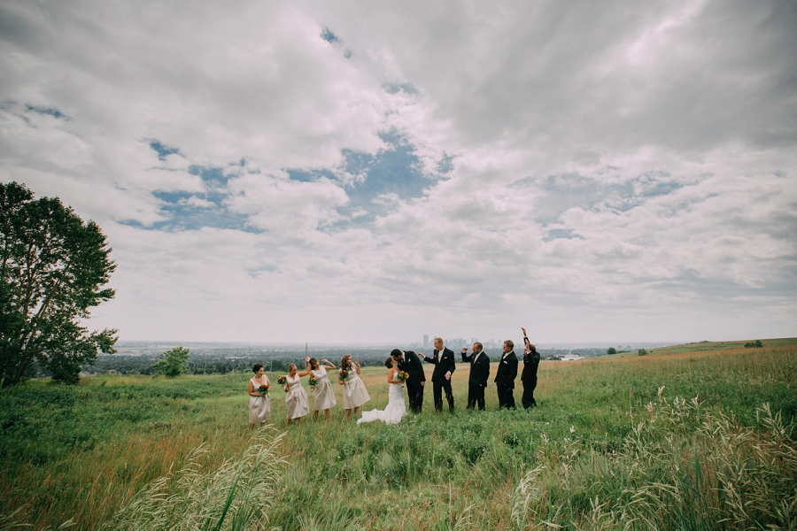 skyline view bride groom kissing bridal party cheering calgary wedding photographer anna michalska