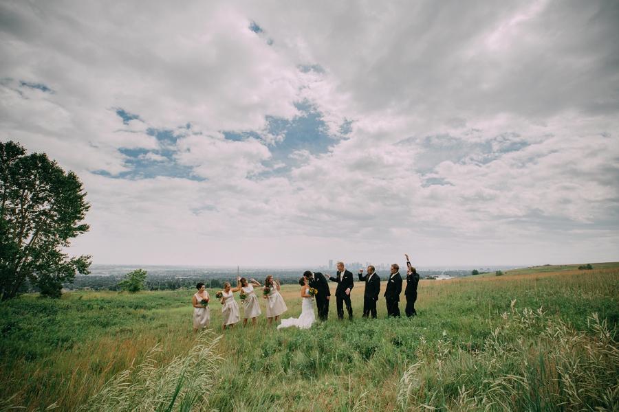 skyline view bride groom kissing bridal party cheering calgary wedding photographer anna michalska