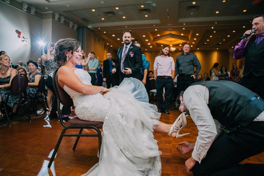 groom getting the garter ramada plaza hotel calgary wedding photographer anna michalska