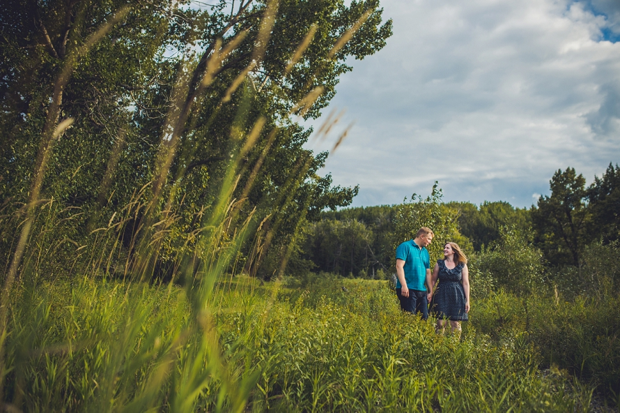 couple walking tall grass fish creek park engagement session calgary wedding photographer anna michalska