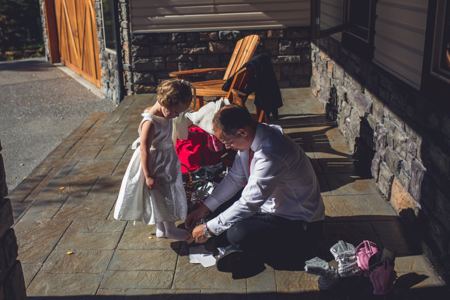 flower girl putting on shoes cowboy themed wedding calgary wedding photographer anna michalska