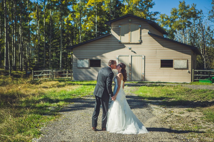 bride groom kiss outside of barn cowboy themed wedding calgary wedding photographer anna michalska