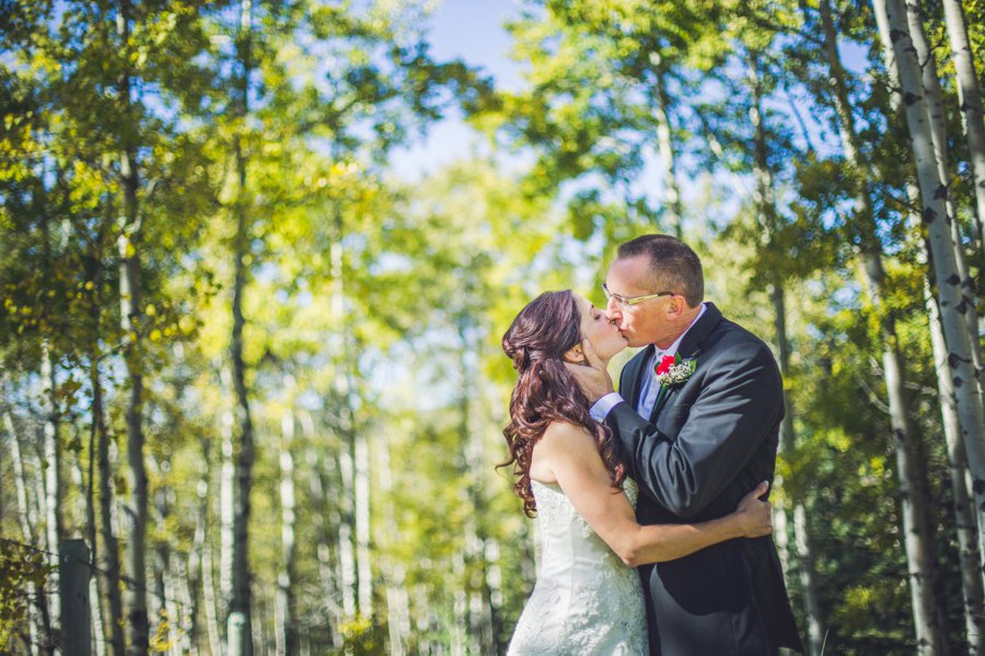 bride groom kiss in forest calgary wedding photographer anna michalska