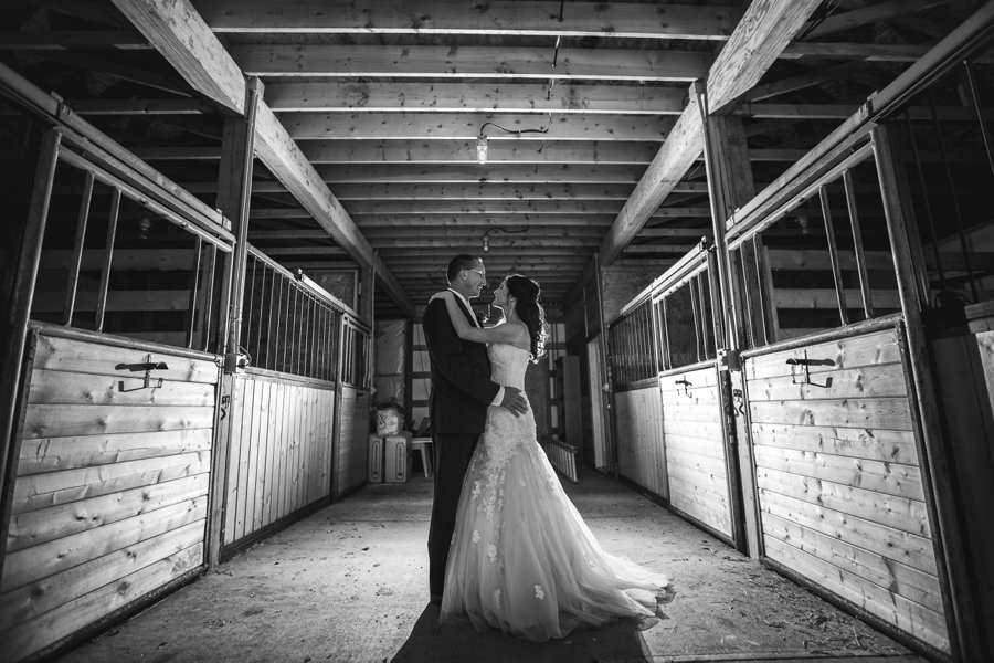 bride groom in barn black and white cowboy themed wedding calgary wedding photographer anna michalska