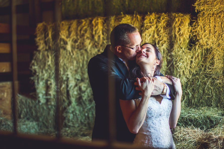groom kisses bride on cheek cowboy themed wedding calgary wedding photographer anna michalska