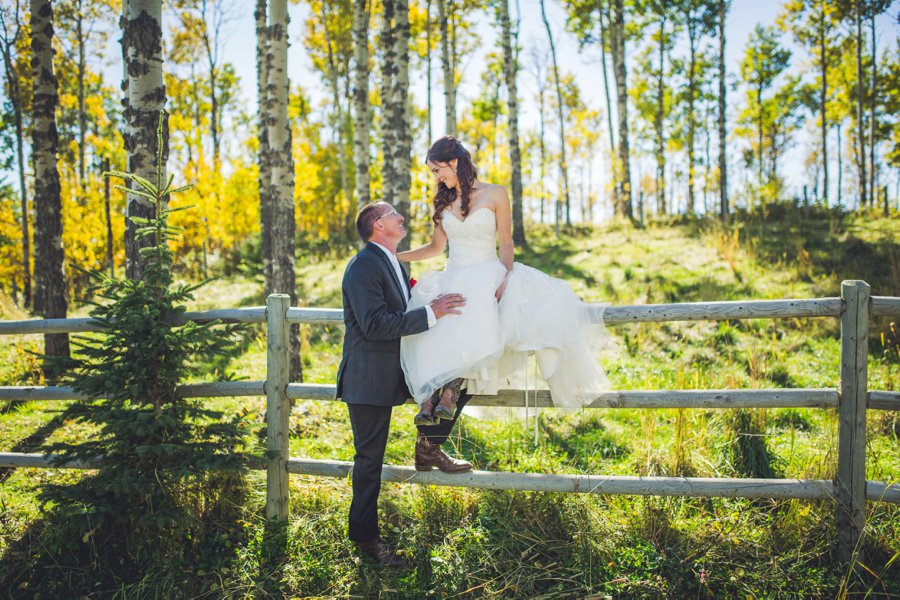 bride sitting on fence cowboy themed wedding calgary wedding photographer anna michalska