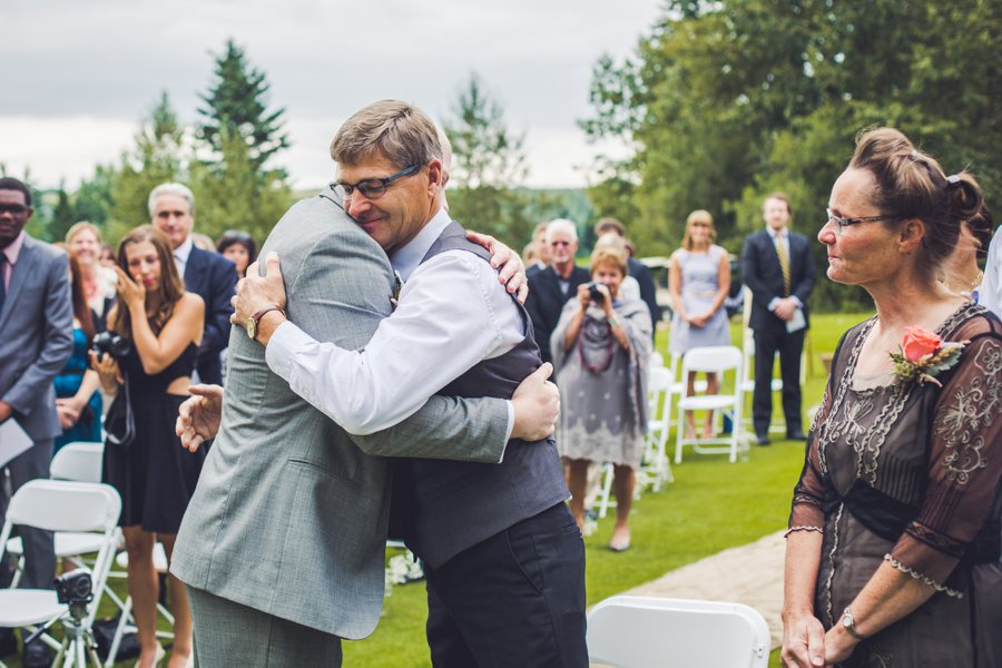 father of bride hugs groom elbow springs golf club calgary wedding photographer anna michalska