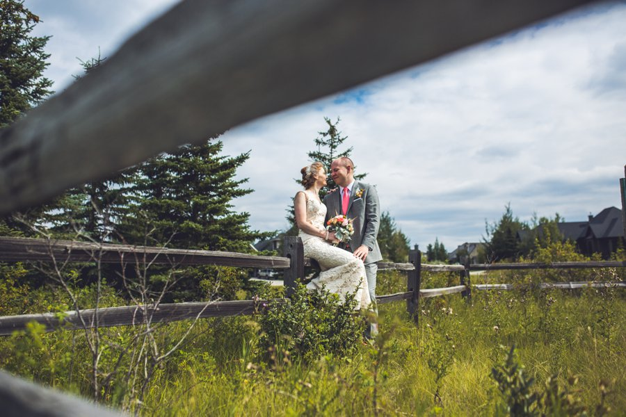 bride groom sitting on fence elbow springs golf club calgary wedding photographer anna michalska
