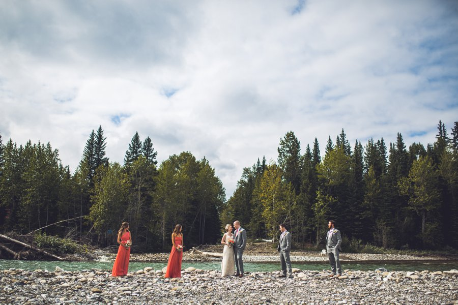 bridal party on rocks with river calgary wedding photographer anna michalska