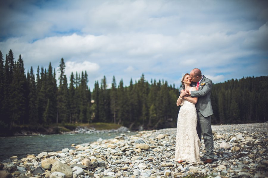 bride groom kiss on rocks with river calgary wedding photographer anna michalska