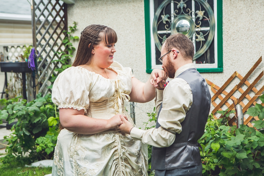 groom kisses bride's hand calgary wedding photographer anna michalska