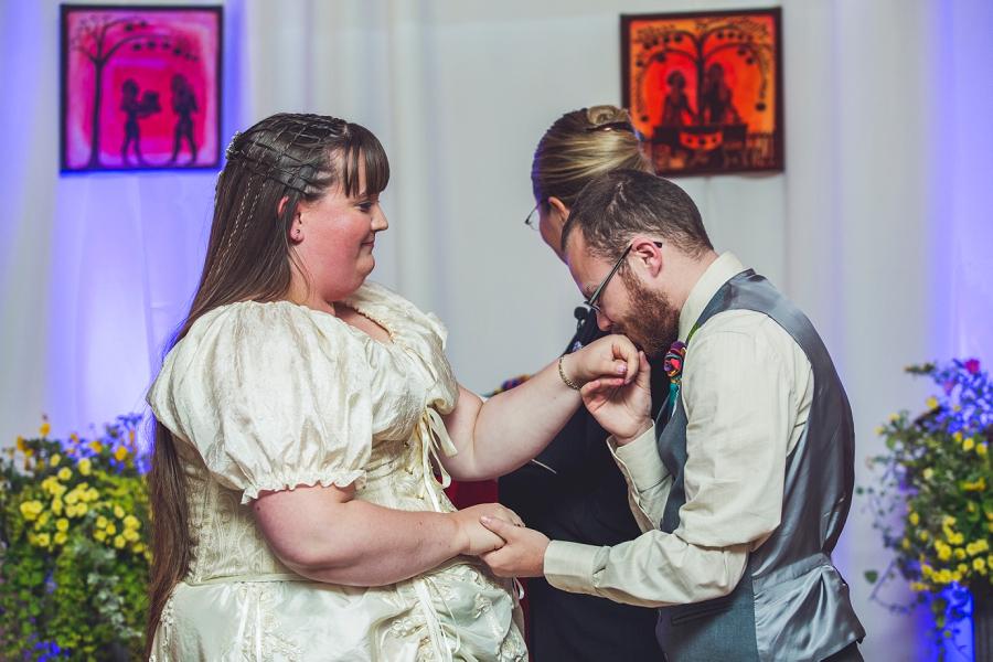 groom kisses bride's hand rainbow wedding calgary wedding photographer anna michalska
