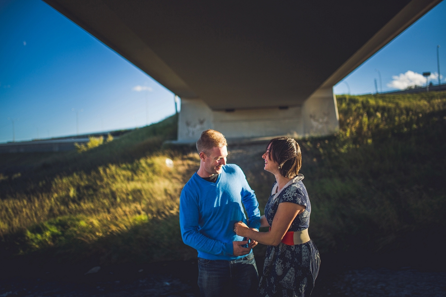 summer engagement session calgary wedding photographer anna michalska couple under bridge laughing
