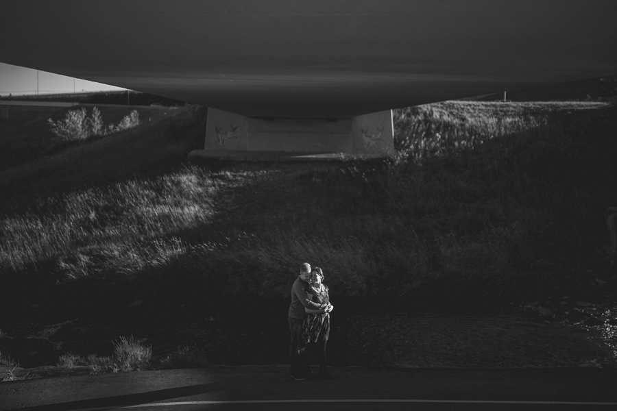 couple under bridge hugging summer engagement session calgary wedding photographer anna michalska