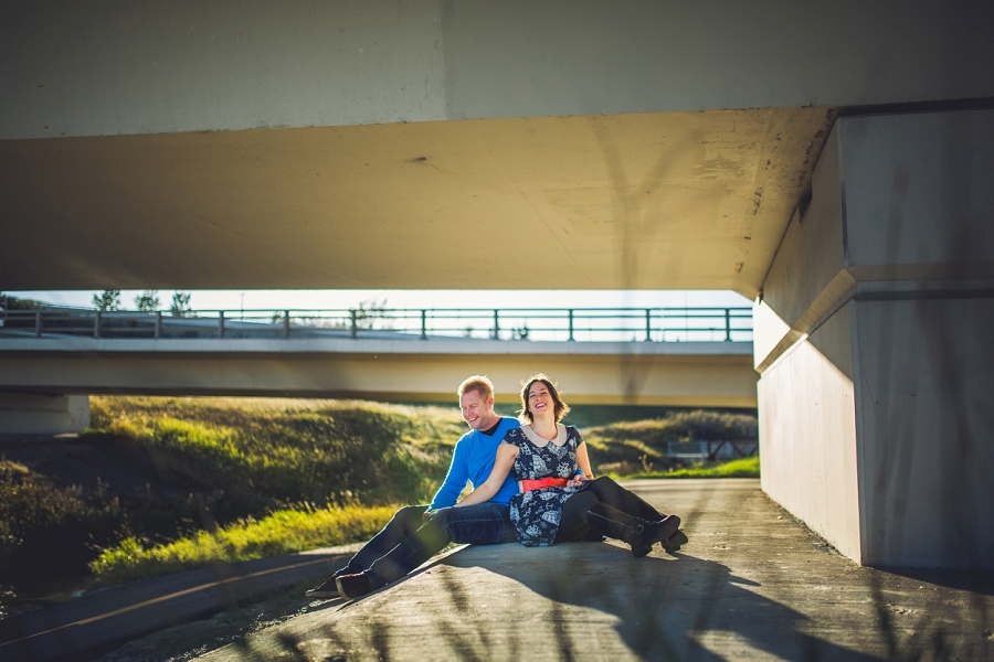 laughing couple sitting under bridge summer engagement session calgary wedding photographer anna michalska