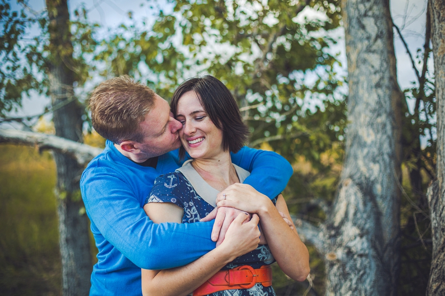 groom kissing bride summer engagement session calgary wedding photographer anna michalska