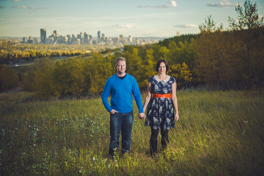 couple standing in field downtown view summer engagement session calgary wedding photographer anna michalska