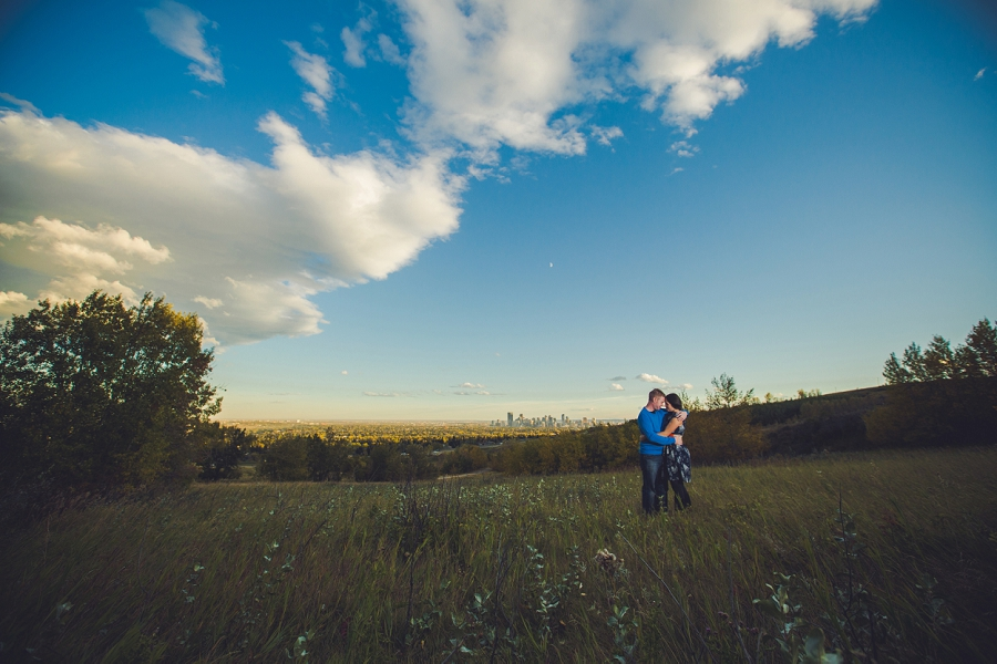 couple cuddling with downtown view summer engagement session calgary wedding photographer anna michalska