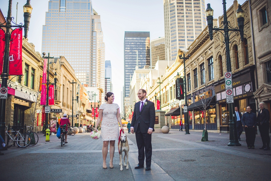 bride groom walking down stephen avenue dog calgary wedding photographer anna michalska