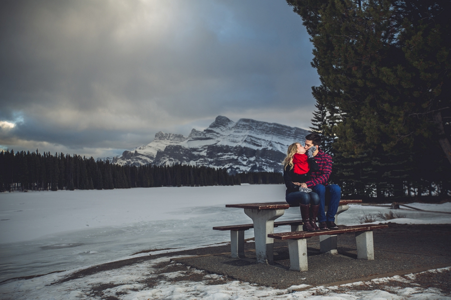 two jack lake couple kissing on picnic bench winter engagement photo