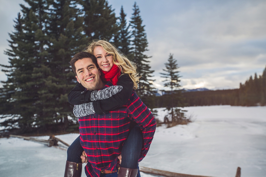 couple piggy back ride winter engagement photos frozen lake
