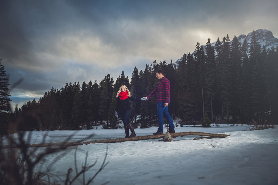 couple on log winter engagement photos two jack lake