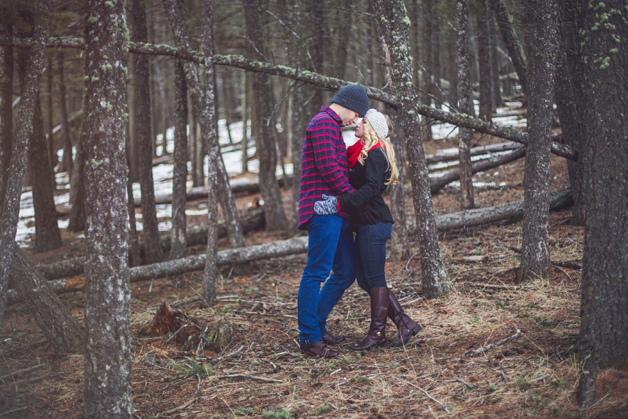 winter engagement photos banff couple in forest