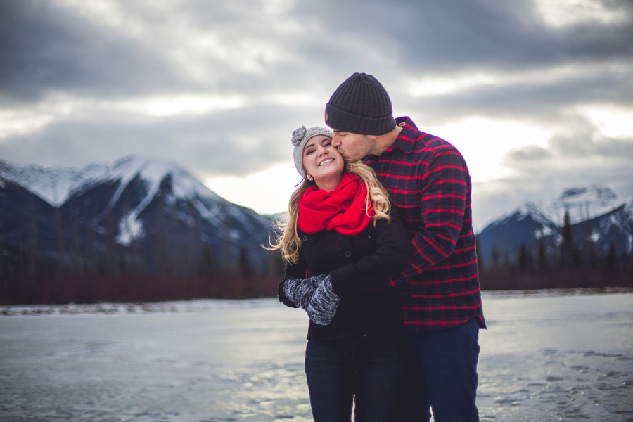 kiss frozen lake vermillion banff winter engagement photo