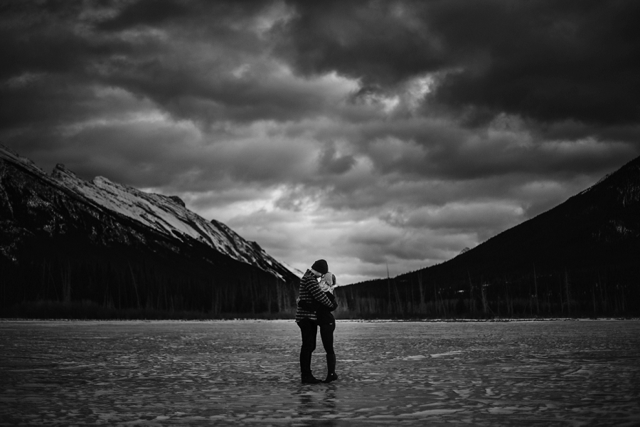 couple on frozen lake winter engagement photos banff vermillion lakes