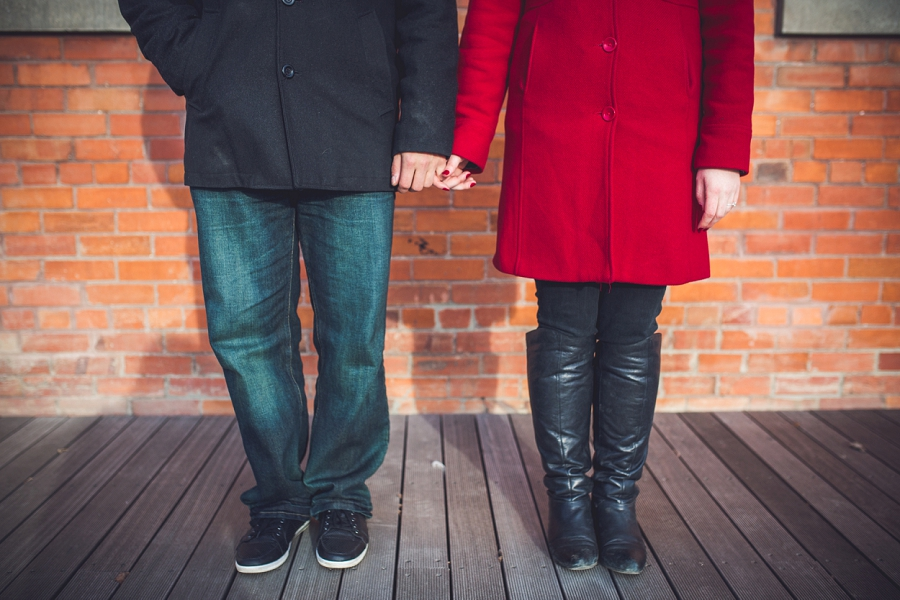 couple holding hands red jacket leather boots red brick wall calgary kensington