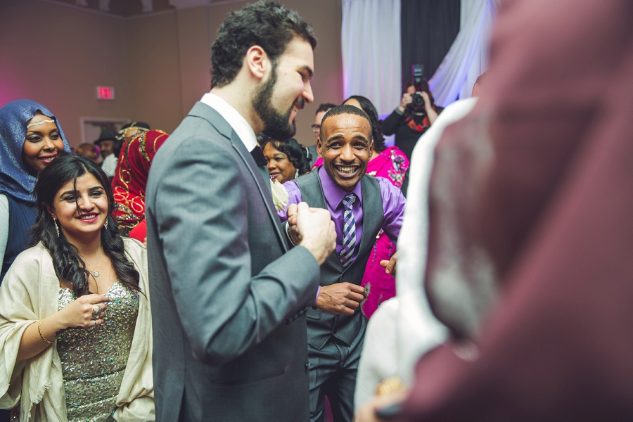 guests laughing dancing multicultural wedding in calgary photographer ramada plaza hotel