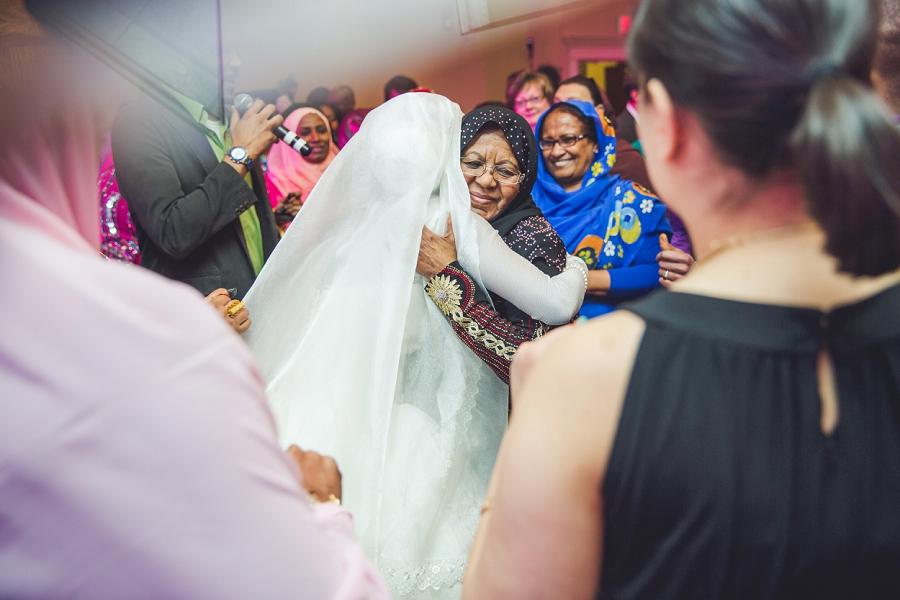 bride getting hug from grandma multicultural islamic wedding in calgary photographer ramada plaza hotel