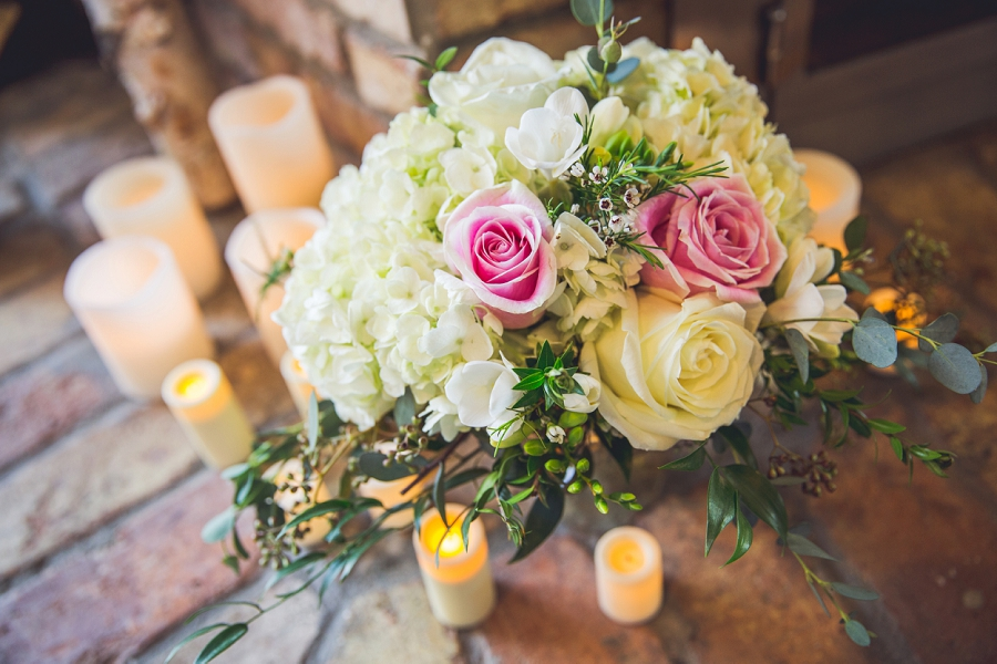rose wedding bouquet with candles around fireplace calgary wedding photographer