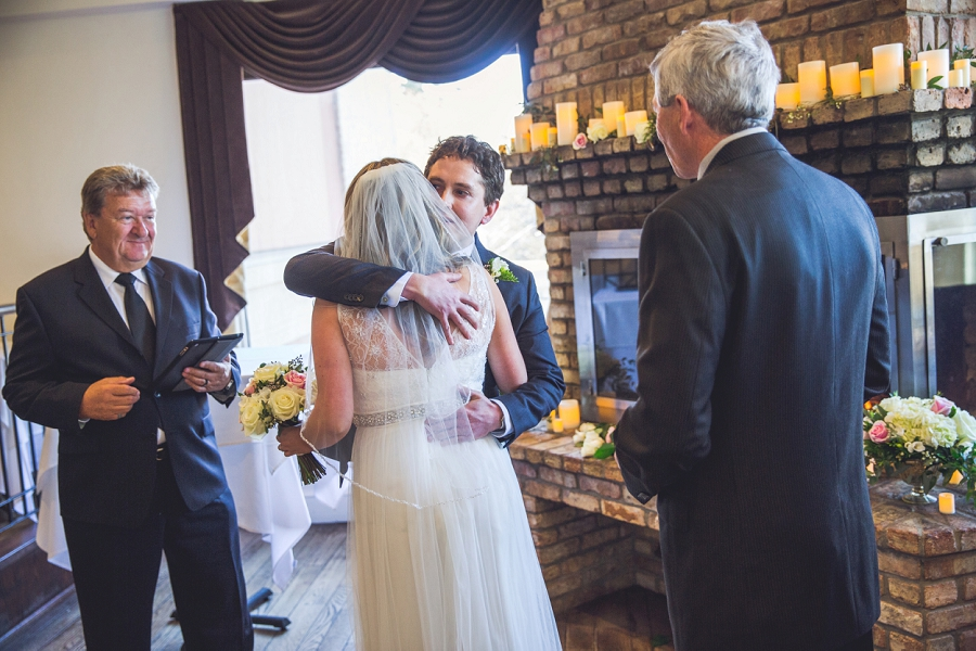 groom hugs bride q haute cuisine calgary wedding photographer