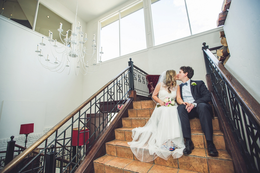 bride groom kissing on steps q haute cuisine calgary wedding photographer