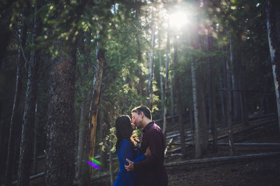trees forest area couple kissing calgary wedding photographer anna michalska