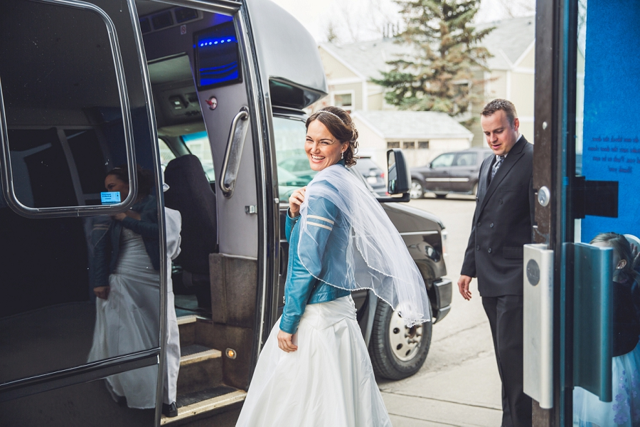 bride in blue leather jacket arrives to church st. anthony's parish calgary wedding photography