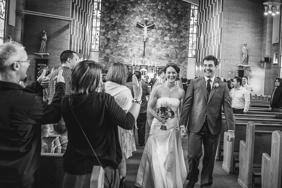 bride and groom exit church st. anthony's parish calgary wedding photography pi day