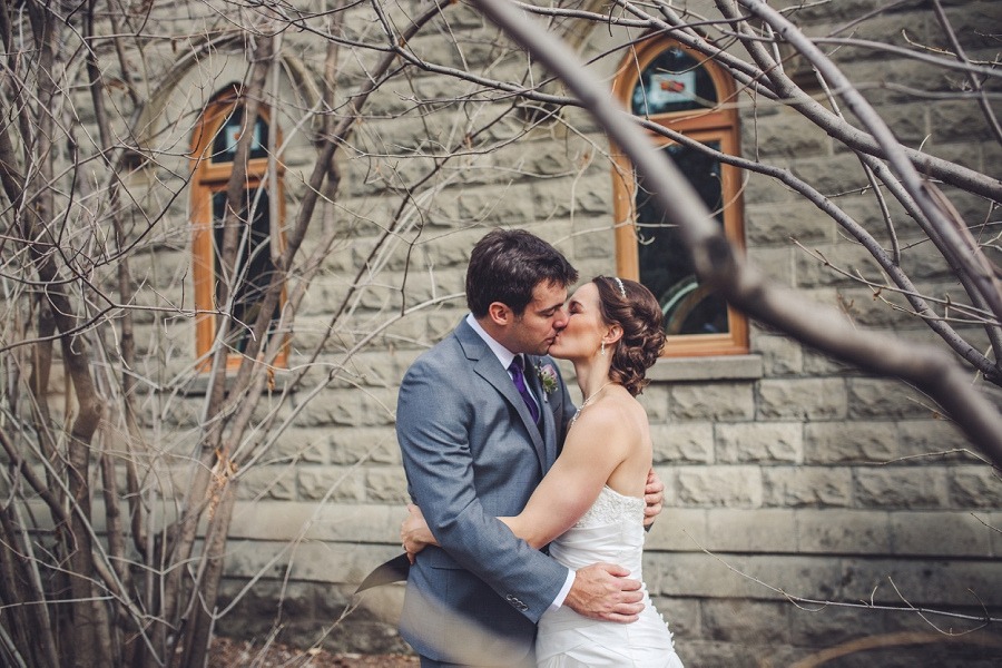 bride kissing groom white stone building reader rock gardens calgary wedding photography pi day