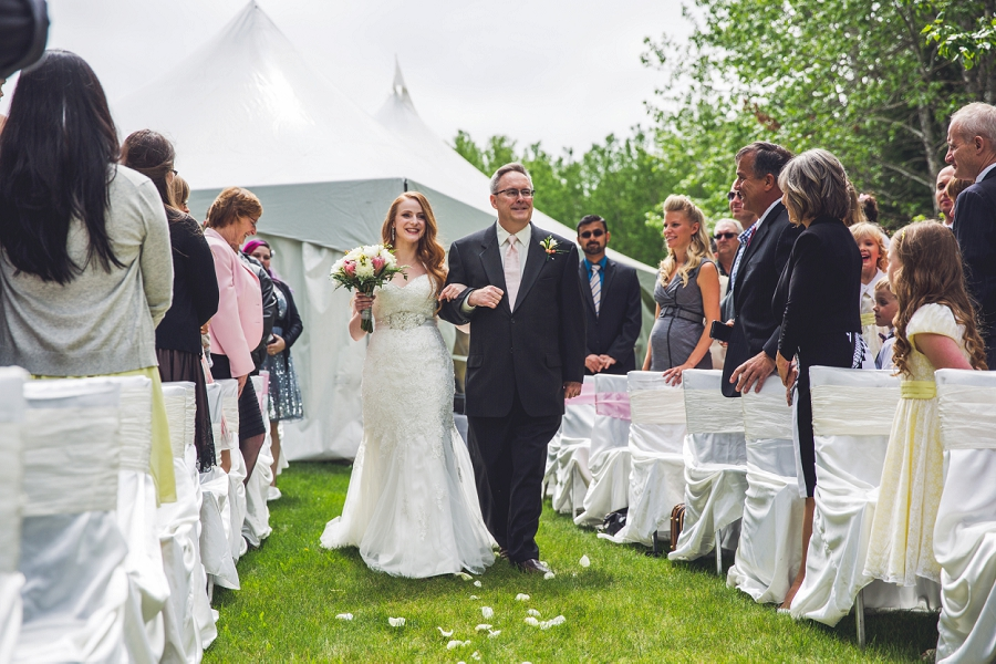 bride smiling walking down aisle with father calgary wedding