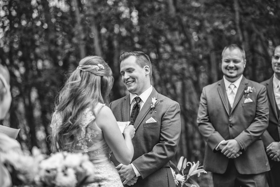 groom laughing at vows calgary backyard wedding ceremony