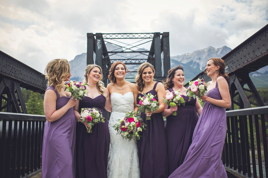 bride with bridesmaids laughing engine bridge canmore