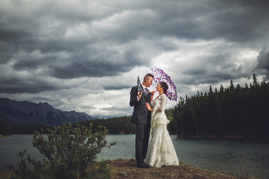 bride and groom with umbrellas stormy clouds mountains canmore