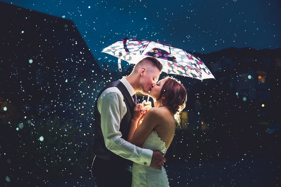 bride groom kiss in the rain cornerstone theatre canmore wedding