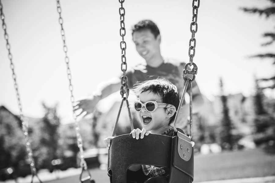 child laughing in swing with dad calgary family photography