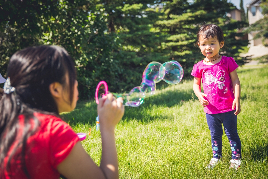 mom blowing bubbles with daughter calgary family photography