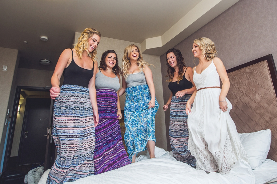 bridal party jumping on bed acclaim hotel calgary wedding bride getting ready