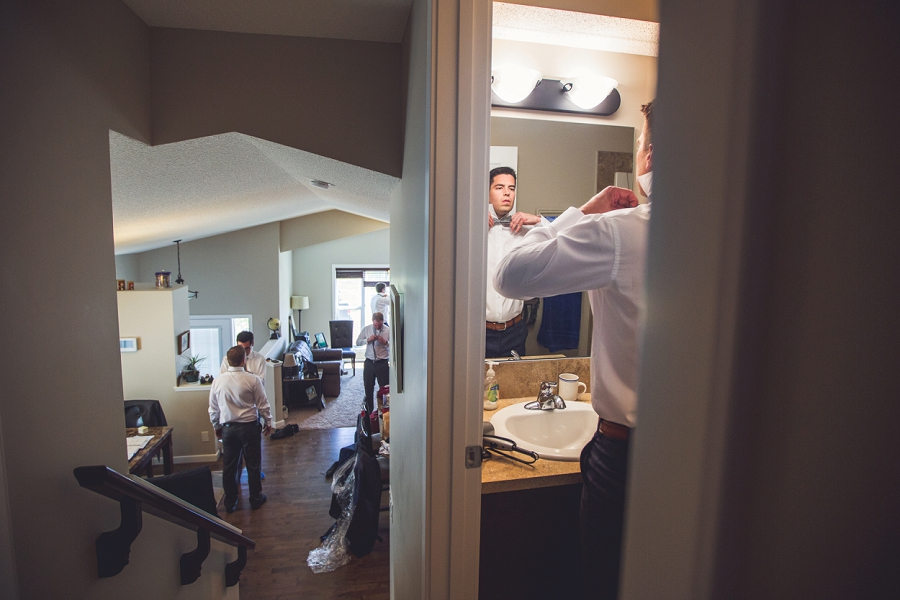 groom groomsmen getting ready bowtie in bathroom