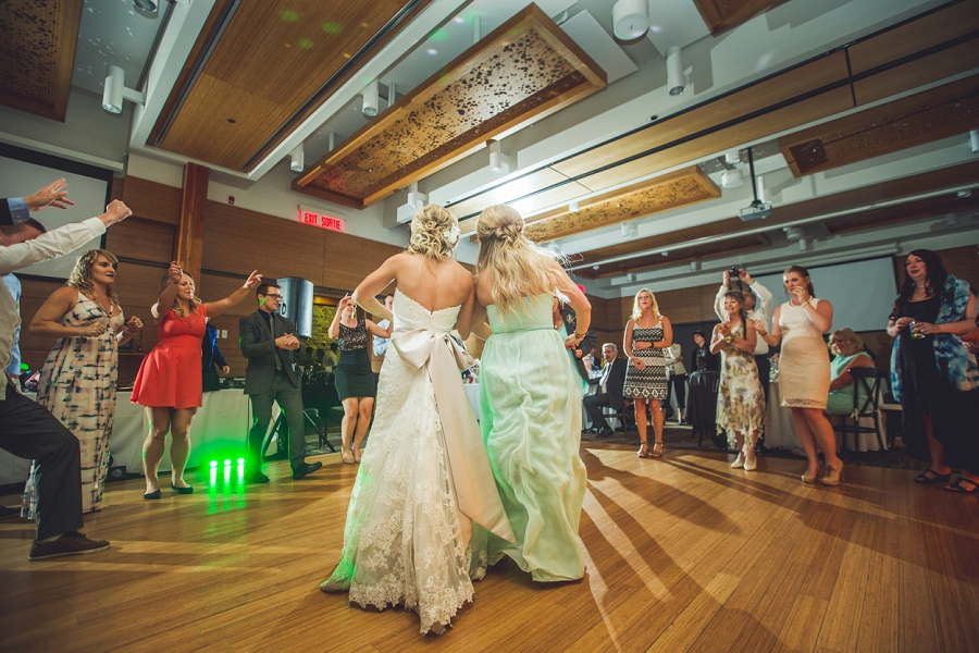 bride with bridesmaid dancing calgary zoo summer wedding